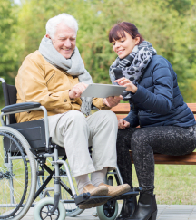 caregiver and elder man in a wheelchair using tablet