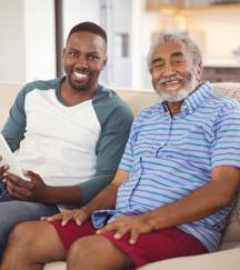 caregiver and elder man smiling