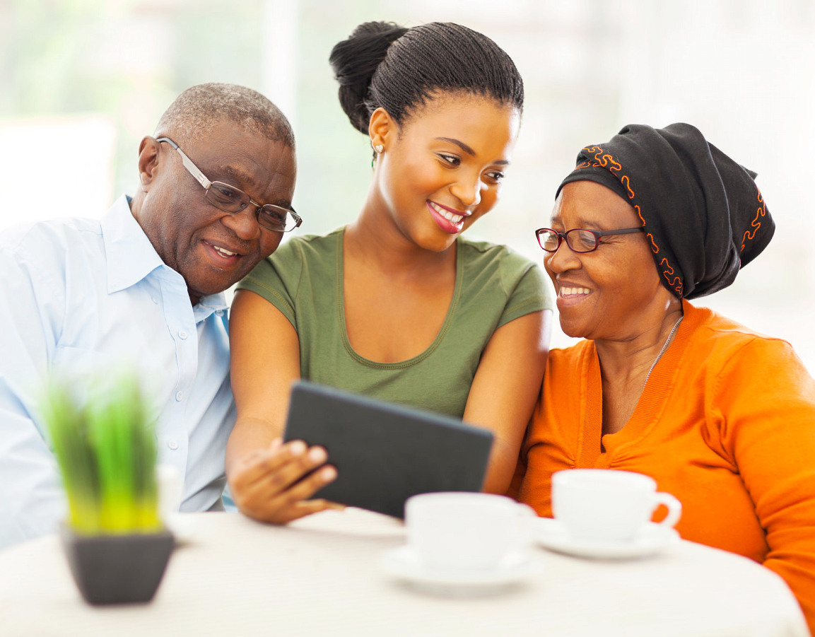 caregiver and elderly couple looking at the tablet