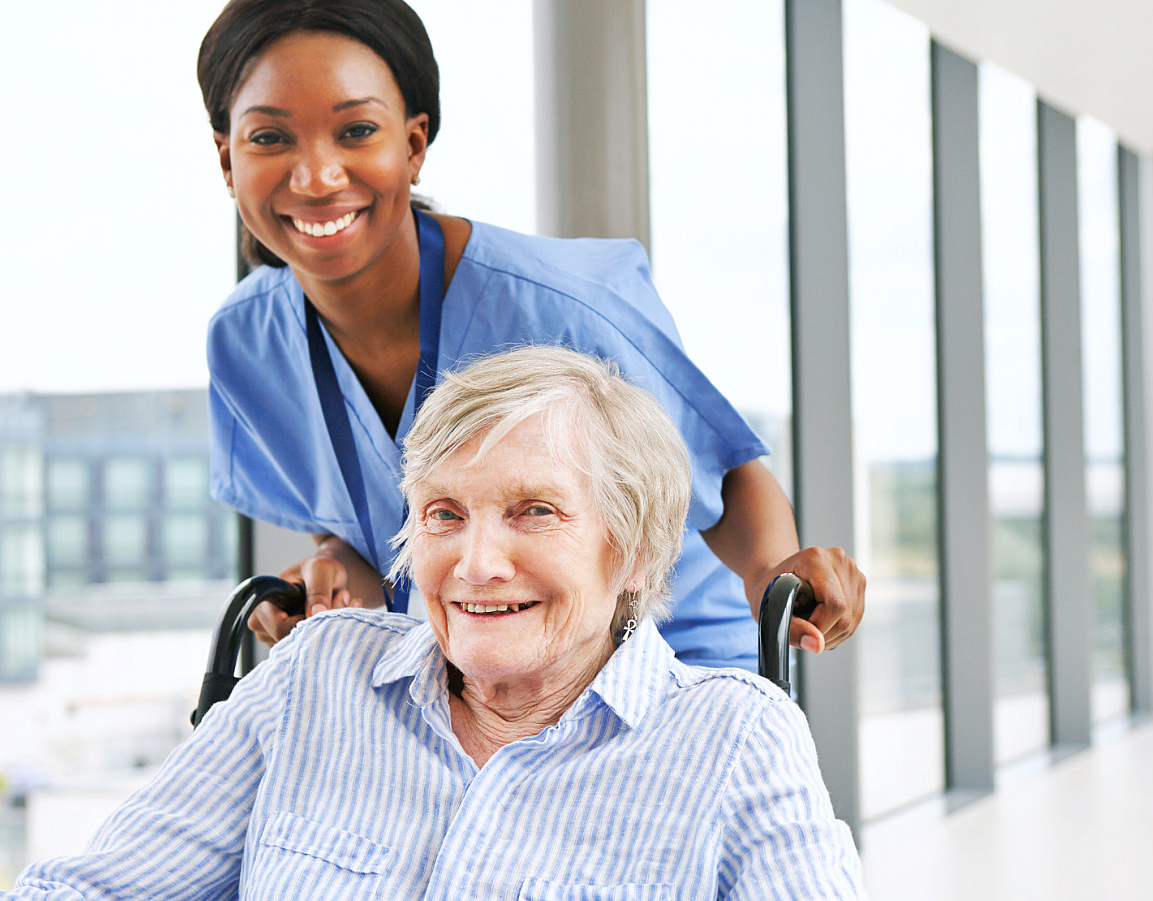 caregiver and elder woman in a wheelchair smiling